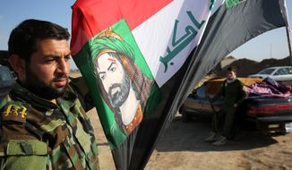 In this Sunday, Feb. 15, 2015, photo, a Shiite militia fighter holds an Iraqi flag with the image of Imam Hussein, the grandson of the Prophet Muhammed, outside of Kirkuk, Iraq. (AP Photo/Emad Matti)