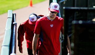 Washington Nationals pitcher Doug Fister, right, leaves the field with bullpen catcher Octavio Martinez after an informal spring training baseball workout, Wednesday, Feb. 18, 2015, in Viera, Fla. (AP Photo/David Goldman)