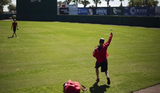 Washington Nationals bullpen catcher Octavio Martinez, right, throws the ball to pitcher Doug Fister during an informal spring training baseball workout, Wednesday, Feb. 18, 2015, in Viera, Fla. (AP Photo/David Goldman)