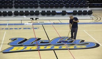 Worker Ruben Monter mops up the floor at Pauley Pavillion Wednesday July 30, 2014 in Los Angeles. A ruptured 93-year-old water main on Tuesday left the UCLA campus awash in 8 million gallons of water in the middle of California's worst drought in decades, stranding people in parking garages and floo(...)