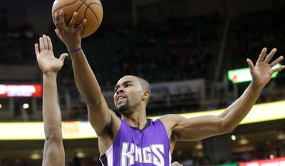 Sacramento Kings guard Ramon Sessions (9) lays the ball as Utah Jazz's Derrick Favors (15) defends and Dante Exum (11) looks on in the first quarter during an NBA basketball game Saturday, Feb. 7, 2015, in Salt Lake City. (AP Photo/Rick Bowmer)