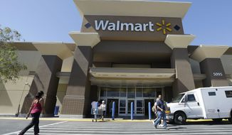 FILE - In this Sept. 19, 2013 file photo, customers walk outside of a Wal-mart store in San Jose, Calif. Wal-Mart Stores Inc. reports quarterly financial results before the market opens Thursday, Feb. 19, 2015. (AP Photo/Jeff Chiu, File)