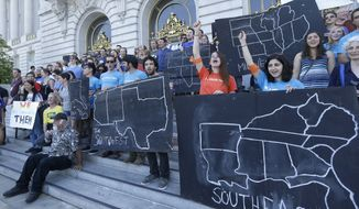 College students and supporters hold up signs at a rally to support fossil fuel divestment outside City Hall in San Francisco. (Associated Press)