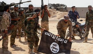 Iraqi security forces hold a flag of the Islamic State group they captured during an operation outside Amirli, some 105 miles (170 kilometers) north of Baghdad, Iraq, on Oct. 7, 2014. (Associated Press) **FILE**
