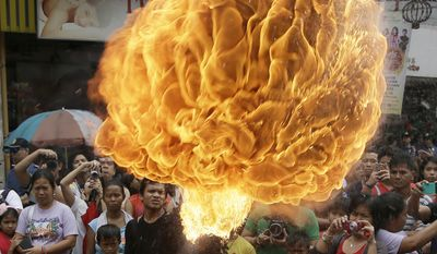 """A fire-eater performs at Manila's Chinatown to celebrate the Chinese New Year Thursday, Feb. 19, 2015 in Manila, Philippines. This year marks the """"Year of the Sheep"""" in the Chinese Lunar calendar. (AP Photo/Bullit Marquez)"""