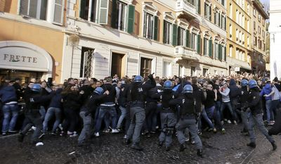 Italian policemen clash with Feyenoord's fans at the Spanish steeps, in downtown Rome, prior to the Europa League soccer match between Roma and Feyenoord, Thursday, Feb. 19, 2015. (AP Photo/Gregorio Borgia)