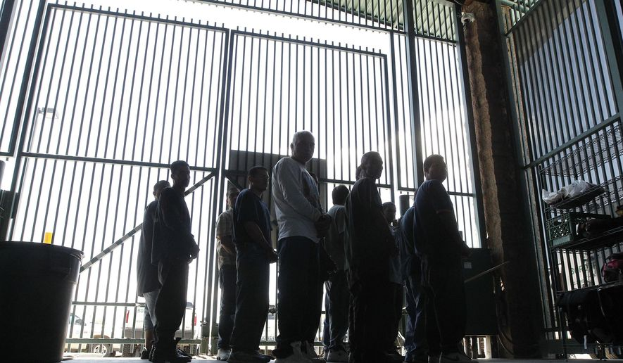 In this file photo from Thursday Aug. 9, 2012, persons are detained for being in the country illegally and are transferred out of the holding area after being processed at the Tucson Sector of the U.S. Customs and Border Protection headquarters in Tucson, Ariz.  A report by a bipartisan think tank that oversees the implementation of 9/11 Commission recommendations and other Homeland Security issues says the department that oversees the U.S. Border Patrol does not use effective performance measurements. (AP Photo/Ross D. Franklin, file)