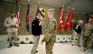 U.S. Defense Secretary Ash Carter, left, speaks with a soldier at Kandahar Airfield in Afghanistan, Sunday, Feb. 22, 2015. Carter is making his first trip to visit troops and commanders in Afghanistan since his swearing-in this week. (AP Photo/Jonathan Ernst, Pool)