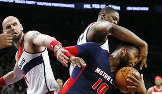 Detroit Pistons' Greg Monroe (10) pulls down a rebound in front of Washington Wizards' Marcin Gortat, left, as he fouled by Washington Wizards' Kevin Seraphin in the second half of an NBA basketball game, Sunday, Feb. 22, 2015, in Auburn Hills, Mich. (AP Photo/Paul Sancya)