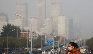 A woman wearing a mask to protect herself from pollutants walks on a pedestrian bridge as buildings at Beijing's Central Business District (Associated Press)