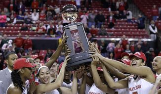 Maryland players hold up a trophy for winning the Big Ten regular-season title after an NCAA college basketball game against Penn State, Monday, Feb. 23, 2015, in College Park, Md. Maryland won 65-34. (AP Photo/Patrick Semansky)