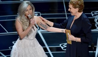 Lady Gaga, left, and Julie Andrews speak at the Oscars on Sunday, Feb. 22, 2015, at the Dolby Theatre in Los Angeles. (Photo by John Shearer/Invision/AP)