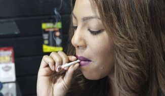 Alaska Cannabis Club CEO Charlo Greene smokes a joint at the medical marijuana dispensary in Anchorage, Alaska, in this Feb. 20, 2015 photo. On Tuesday, Feb. 24, 2015, Alaska will become the third state in the nation to legalize marijuana. (AP Photo/Mark Thiessen)