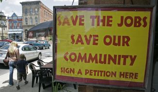 FILE - In this June 5, 2008 file photo, a sign hangs outside a bookstore in downtown Wilmington, Ohio When DHL switched its ground sorting and handling to UPS in 2008, the area lost about 7,000 ABX Air and ASTAR Air Cargo jobs at the Wilmington Air Park. Ohio governor John Kasich will spotlight the slowly rebounding city by delivering his State of the State address there Feb. 24, 2015. (AP Photo/Al Behrman, File)