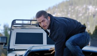 "In this photo provided by Universal Pictures, Paul Walker as Brian makes his move in ""Furious 7,"" directed by James Wan. The hugely successful ""Fast & Furious"" movie franchise is hitching a ride with the massively popular ""Forza"" racing game series. ""Forza"" developer Turn 10 Studios and ""Fast & Furious"" distributor Universal are collaborating on a stand-alone video game pegged to the upcoming release of ""Furious 7."" (AP Photo/Universal Pictures)"