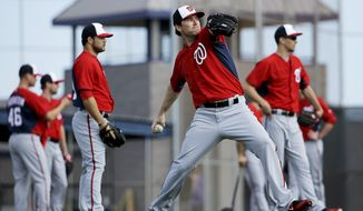 Washington Nationals pitcher Casey Janssen thaws the ball during a spring training baseball workout, Sunday, Feb. 22, 2015, in Viera, Fla. (AP Photo/David Goldman)