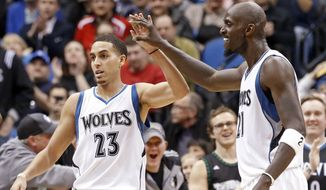 Minnesota Timberwolves' Kevin Garnett, right, congratulates Kevin Martin after a basket in the second half of an NBA basketball game, Wednesday, Feb. 25, 2015, in Minneapolis. The Timberwolves won 97-77. Martin led his team with 28 points. (AP Photo/Jim Mone)