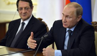 Russian President Vladimir Putin, right, speaks at a joint news conference with Cyprus' President Nicos Anastasiades, left,  in the Novo-Ogaryovo residence outside Moscow, Russia, Wednesday, Feb. 25, 2015. (AP Photo/Yuri Kadobnov, Pool)