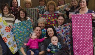 Lori Frollo, far right, family and friends pose after knitting quilts for Neonatal Intensive Care Unit at Covenant Hospital, Tuesday, Feb. 10, 2015 in the basement of the Mercantile Bank in Merrill, Mich. Frollo had this idea after her twin grandchildren, Claire and Cole, were in the Neonatal Intensive Care Unit for seven weeks and wanted to donate some quilts to the facility. (AP Photo/The Saginaw News, Andrew Whitaker)