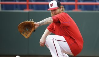 Washington Nationals' Mike Carp fields a throw to first base during a spring training baseball workout, Wednesday, Feb. 25, 2015, in Viera, Fla. (AP Photo/David Goldman)