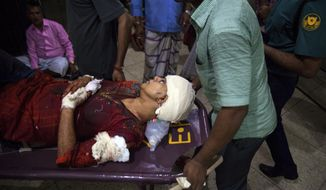 In this Thursday, Feb. 26, 2015, photo , Rafida Ahmed, wife of a prominent Bangladeshi-American blogger, Avijit Raoy is being rushed to hospital on a stretcher after she was seriously injured by unidentified attackers, in Dhaka, Bangladesh. Roy, who was known for speaking out against religious fundamentalism was hacked to death in the streets of Bangladesh's capital as he walked with his wife, police said Friday. (AP Photo/Rajib Dhar)