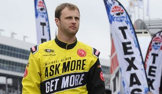 Travis Kvapil walks the track before a rain delayed start for the NASCAR Sprint Cup Series auto race at Texas Motor Speedway in Fort Worth, Texas, Sunday, April 6, 2014. (AP Photo/Ralph Lauer)