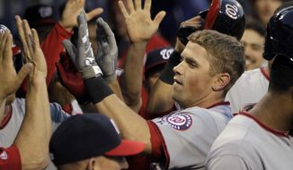 Washington Nationals' Tyler Moore is cheered in the dugout after hitting a home run in the third inning of a baseball game against the Philadelphia Phillies, Friday, May 2, 2014, in Philadelphia. (AP Photo/Laurence Kesterson)