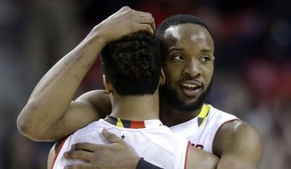 Maryland guard/forward Dez Wells, right, hugs teammate Melo Trimble in the final moments of an NCAA college basketball game against Michigan, Saturday, Feb. 28, 2015, in College Park, Md. Wells and Trimble contributed a combined 32 points in Maryland's 66-56 win. (AP Photo/Patrick Semansky)