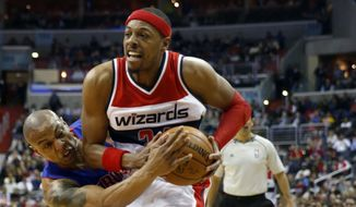 Detroit Pistons forward Caron Butler (31) reaches for the ball in the hands of Washington Wizards forward Paul Pierce (34) in the second half of an NBA basketball game Saturday, Feb. 28, 2015, in Washington. The Wizards won 99-95. (AP Photo/Alex Brandon)