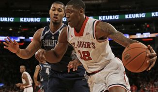 St. John's forward Chris Obekpa (12) drives past Georgetown forward Mikael Hopkins during the second half of an NCAA college basketball game,  Saturday, Feb. 28, 2015, at Madison Square Garden in New York. St. John's won 81-70. (AP Photo/Mary Altaffer)