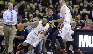 Maryland guard/forward Dez Wells, left, drives around Michigan guard/forward Aubrey Dawkins as Dawkins' is screened by Maryland forward Evan Smotrycz in the first half of an NCAA college basketball game, Saturday, Feb. 28, 2015, in College Park, Md. (AP Photo/Patrick Semansky)