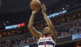 Washington Wizards guard Bradley Beal (3) shoots the ball as Detroit Pistons head coach Stan Van Gundy, standing left, watches in the second half of an NBA basketball game Saturday, Feb. 28, 2015, in Washington. The Wizards won 99-95. (AP Photo/Alex Brandon)