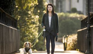 In this Feb. 25, 2015, photo, Ebola survivor Nina Pham walks in a park with her dog Bentley in Dallas. Pham told The Dallas Morning News in the interview that she is preparing to file a lawsuit Monday, March 2, in Dallas County against Texas Health Resources. (AP Photo/The Dallas Morning News, Smiley N. Pool)