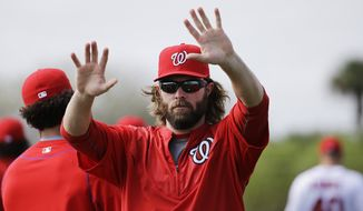 Washington Nationals' Jayson Werth waves to fans while stretching with teammates during a spring training baseball workout, Sunday, March 1, 2015, in Viera, Fla. (AP Photo/David Goldman)