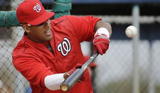 Washington Nationals' Yunel Escobar bunts during a spring training baseball workout, Sunday, March 1, 2015, in Viera, Fla. (AP Photo/David Goldman)