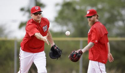 Washington Nationals' Ryan Zimmerman, left, tosses the ball toward first base during a drill with teammate Mike Carp, right, at a spring training baseball workout, Sunday, March 1, 2015, in Viera, Fla. (AP Photo/David Goldman)