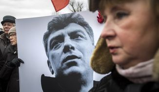 People carry a placard with the image of opposition leader Boris Nemtsov who was gunned down on Friday, during a march, in St. Petersburg, Russia, Sunday, March 1, 2015. (AP Photo/Elena Ignatyeva)