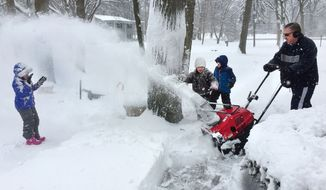 Allison Brady, left, gets a blast of snows from her father Peter Brady's snowblower as he clears their sidewalk Sunday, March 1, 2015, in Indianapolis. Gabby Deer, and Allison's brother, Alex, second from right, watch the fun. March roared into Indiana on Sunday, dumping 8 inches or more of snow in some areas and bringing a threat of possible flooding early this week because of expected rain and snow melt. (AP Photo/The Indianapolis Star, Charlie Nye)