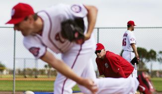Washington Nationals manager Matt Williams, right, watches as pitcher Max Scherzer warms up in the bullpen during a spring training baseball workout, Sunday, March 1, 2015, in Viera, Fla. (AP Photo/David Goldman)