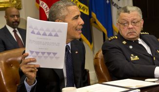 Philadelphia Police Commissioner Charles Ramsey watches at right as President Barack Obama holds up a copy of the interim report of the President's Task Force on 21st Century Policing, Monday, March 2, 2015, during a meeting with members of the task force in the Roosevelt Room of the White House in Washington. (AP Photo/Jacquelyn Martin)