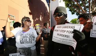 Suzette Shaw, left, a homeless woman, joins others protesting a police shooting of a homeless man on Tuesday, March 3, 2015, in downtown Los Angeles. There was a moment of silence at the site of the shooting where several dozen people rallied Tuesday in protest. (AP Photo/Nick Ut) ** FILE **