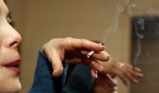 Rica Madrid poses for a photograph as she smokes pot in her home on the first day of legal possession of marijuana for recreational purposes, Thursday, Feb. 26, 2015 in Washington. Democratic Mayor Muriel Bowser defied threats from Congress by implementing a voter-approved initiative on Thursday, making the city the only place east of the Mississippi River where people can legally grow and share marijuana in private. (AP Photo/Alex Brandon)
