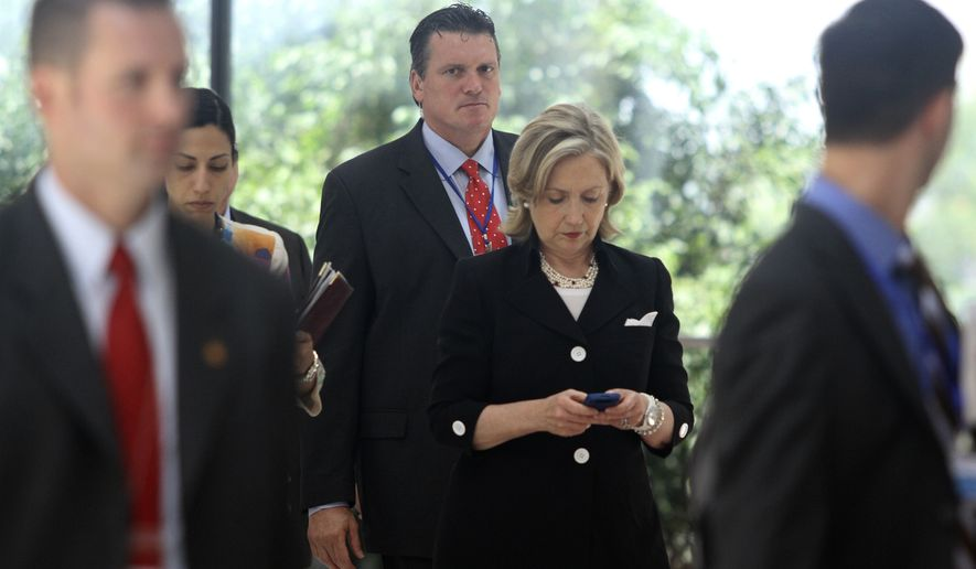 Secretary of State Hillary Rodham Clinton checks her phone after attending a U.S.-Russia meeting in Hanoi, Vietnam on July 23, 2010. The revelation that Mrs. Clinton used an off-the-books email account during her time as secretary of state has raised fresh questions about her credibility heading into 2016. (Associated Press)