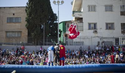 Acrobats performs for children of foreign migrant workers during a Purim party in Tel Aviv, Israel, Tuesday, March 3, 2015. The Jewish holiday of Purim commemorates the Jews' salvation from genocide in ancient Persia, as recounted in the Book of Esther, which is read in synagogues. Other customs include: sending food parcels and giving charity; dressing up in masks and costumes; eating a festive meal; and public celebrations. (AP Photo/Ariel Schalit)