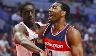 Washington Wizards guard John Wall (2) is fouled on the way to the basket by Chicago Bulls forward Tony Snell during the first half of an NBA basketball game, Tuesday, March 3, 2015, in Chicago. (AP Photo/Kamil Krzaczynski)