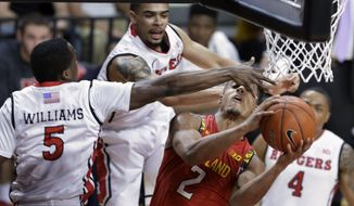 Rutgers guard Mike Williams tries to block a shot by Maryland guard Melo Trimble (2) during the first half of an NCAA college basketball game Tuesday, March 3, 2015, in Piscataway, N.J. (AP Photo/Mel Evans)