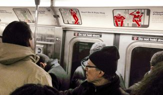 "In this Tuesday, March 3, 2015 photo, subway riders commute on a crowded car in New York. Behind them are signs posted by the Metropolitan Transportation Authority exhorting riders to show more courtesy. One sign displays the message, ""Don't Be A Pole Hog,"" while another shows, ""Clipping? Primping? Everybody wants to look their best, but it's a subway car, not a restroom."" (AP Photo/Richard Drew)"
