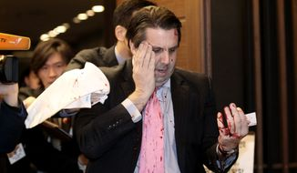 U.S. Ambassador to South Korea Mark Lippert leaves a lecture hall for a hospital in Seoul, South Korea, on March 5 after being attacked by a man wielding a razor. (Associated Press)