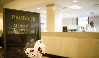 The Birmingham Probate Court sign shows a ribbon welcoming couples to get a marriage license, Wednesday, March 4, 2015, in Birmingham, Ala. Alabama's stand against same-sex marriage regained ground Wednesday after the state's highest court ruled that its ban remains legal, despite federal court pressure to begin issuing licenses to gays and lesbians. (AP Photo/Brynn Anderson)