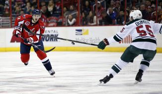 Washington Capitals left wing Curtis Glencross (22) sends the puck past Minnesota Wild defenseman Matt Dumba (55) during the first period of an NHL hockey game Thursday, March 5, 2015, in Washington. (AP Photo/Alex Brandon)